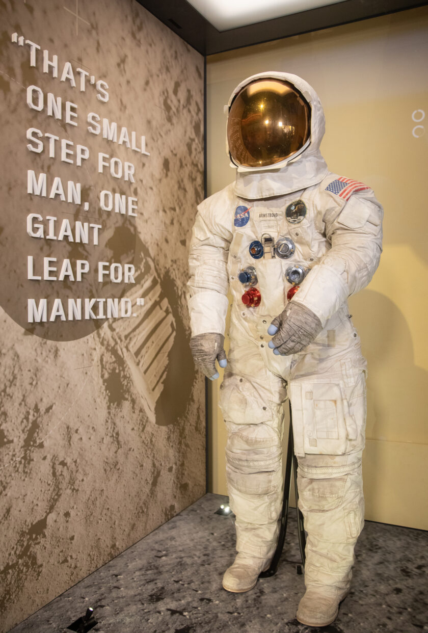 """Neil Armstrong's spacesuit on display with his words from the moon landing """"That's one small step for man, one giant leap for mankind in the background."""